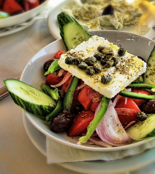 "Santorini traditional salad with capers and caper leaves, cherry tomatoes, local crunchy cucumber ""katsouni"" & fresh made Santorini goat cheese ""chloro"""